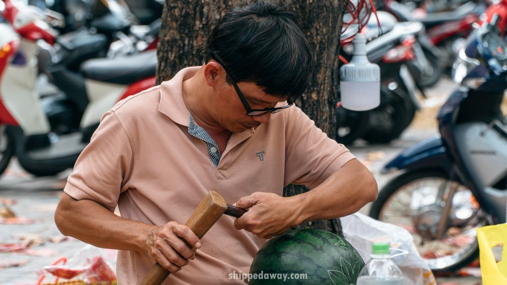 Man on the street carving a watermelon for Tet, Vietnamese New Year