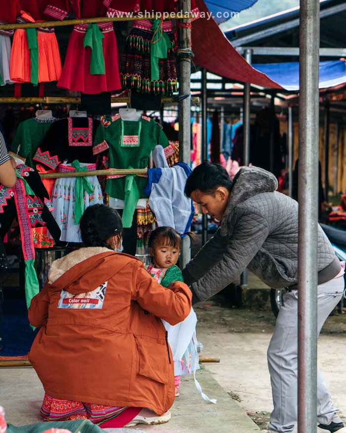 Little girl trying clothes at Pa Co Market in Mai Chau, Vietnam