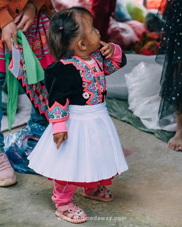 Little girl trying clothes at Pa Co Market in Mai Chau