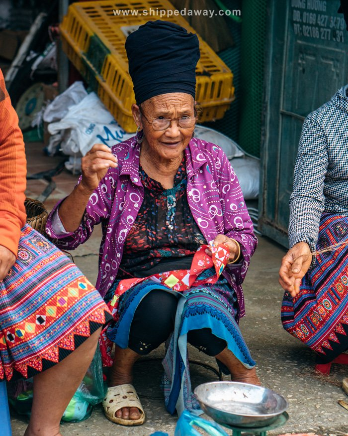 Elder Hmong woman sewing at Pa Co Market in Vietnam
