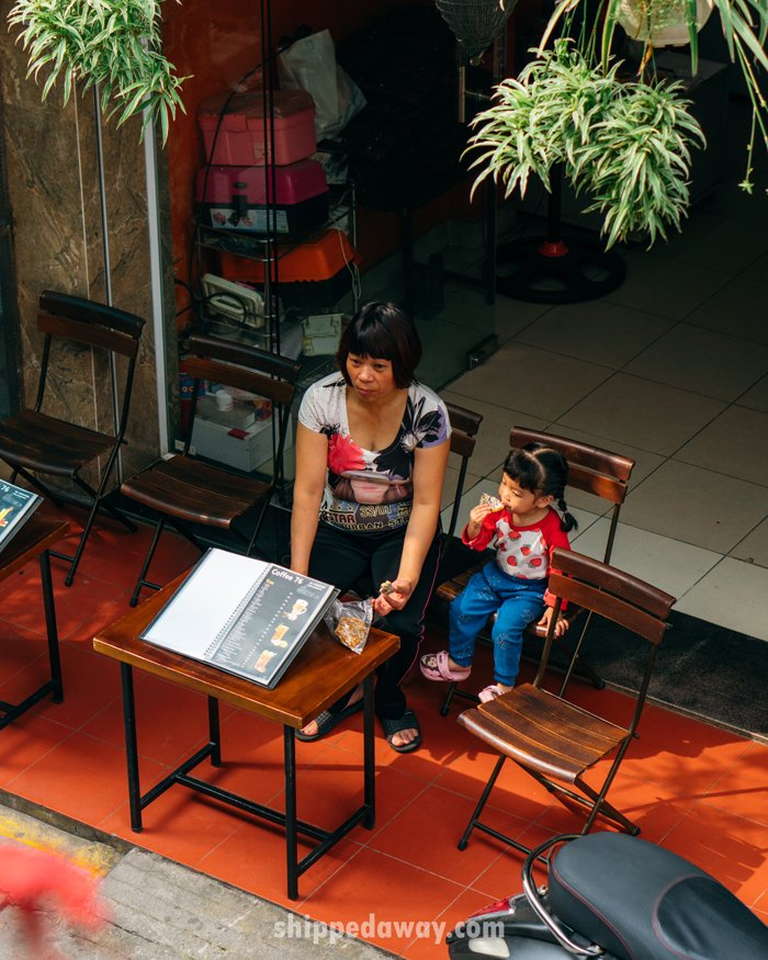 Cafe owner with her child at Hanoi's Train Street